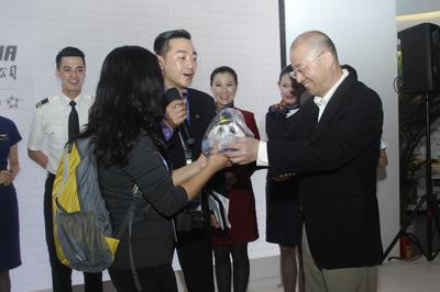 国航党委书记樊澄为幸运旅客送上纪念品